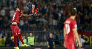 Mitrovic of Serbia grabs a flag depicting so-called Greater Albania that was flown over the pitch during their Euro 2016 Group I qualifying soccer match against Albania at the FK Partizan stadium in Belgrade