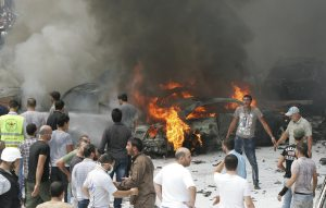 Civil Defence members and residents gather at the site of an explosion, in Beirut's southern suburbs